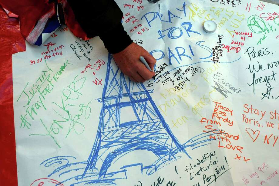 New Yorkers showed their support for France by signing a makeshift card on Saturday, a day after the terrorist attacks in Paris. Photo: JEWEL SAMAD, Staff / AFP