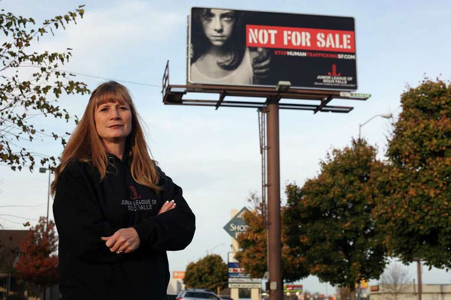 Dawn Stenberg, from the Junior League of Sioux Falls, stands near the group's anti-human trafficking billboard in Sioux Falls, S.D. Photo: Jay Pickthorn /Associated Press / FR156812 AP