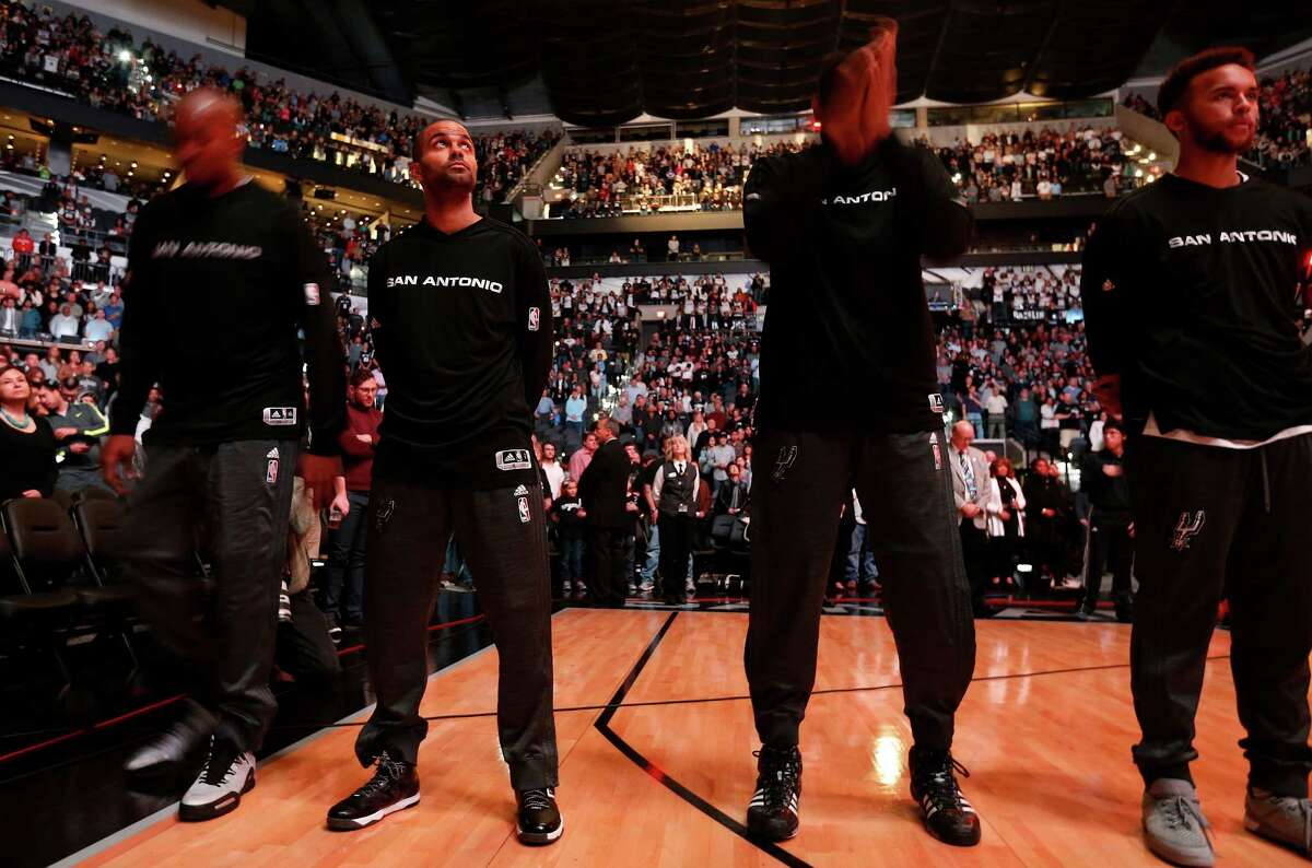 Spurs guard Tony Parker (center) looks up during the playing of the France National Anthem in respect to the country after recent terrorist attacks. Parker and fellow teammate Boris Diaw are both French citizens. (Kin Man Hui/San Antonio Express-News)