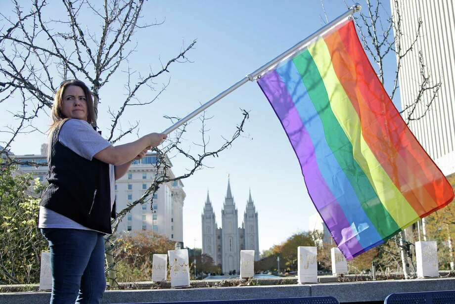 Sandy Newcomb poses for a photograph with a rainbow flag as Mormons gather for a mass resignation from the Church of Jesus Christ of Latter-day Saints on Saturday in Salt Lake City. Photo: Rick Bowmer /Associated Press / AP