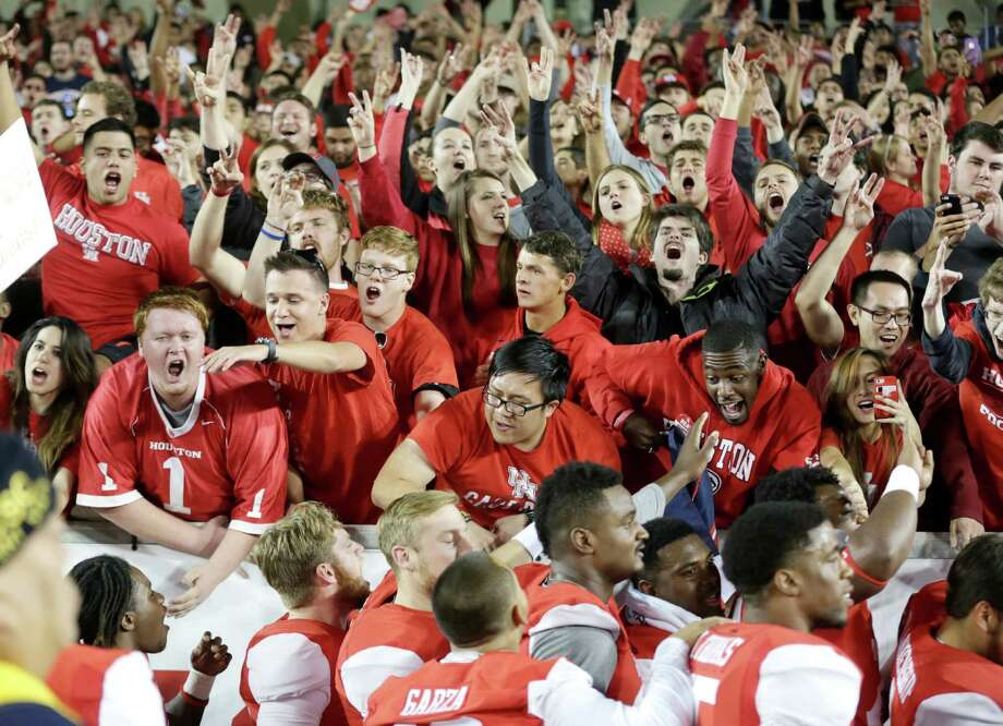 The Cougars celebrate with some of the students who contributed to the overflow crowd of 42,159 on Saturday night. Photo: Jon Shapley, Staff / © 2015 Houston Chronicle