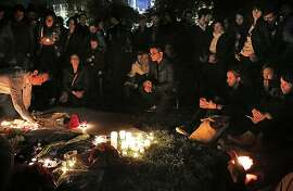 People sit and stand in a large group around a memorial with candles at Yerba Buena Gardens Nov. 14, 2015 in San Francisco, Calif. during one of two vigils held by local people in honor of France and those lost and injured in the terrorist attacks in Paris on Friday night.