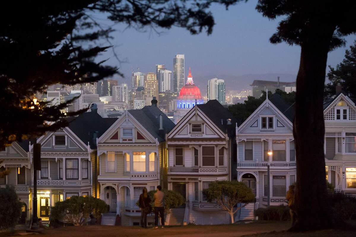 San Francisco's City Hall is illuminated in blue, white and red as seen from the popular tourist location Alamo Square in San Francisco, California on November 14, 2015, one day after the Paris terrorist attacks.