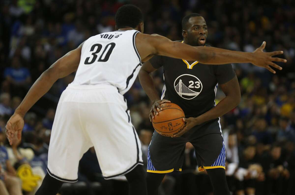 Draymond Green, right, looks for a teammate as he is guarded by Thaddeus Young during the Golden State Warriors vs. the Brooklyn Nets game in the Oracle Arena Nov. 14, 2015 in Oakland, Calif. The Warriors won 107-99 in overtime.