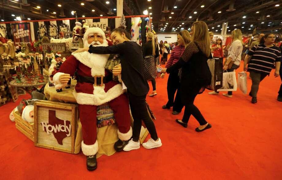 Siyi Tian hugs a giant Santa in the Crooked Antler booth at the Nutcracker Market on Saturday, Nov. 14, 2015, in Houston. Photo: Karen Warren, Houston Chronicle / © 2015 Houston Chronicle