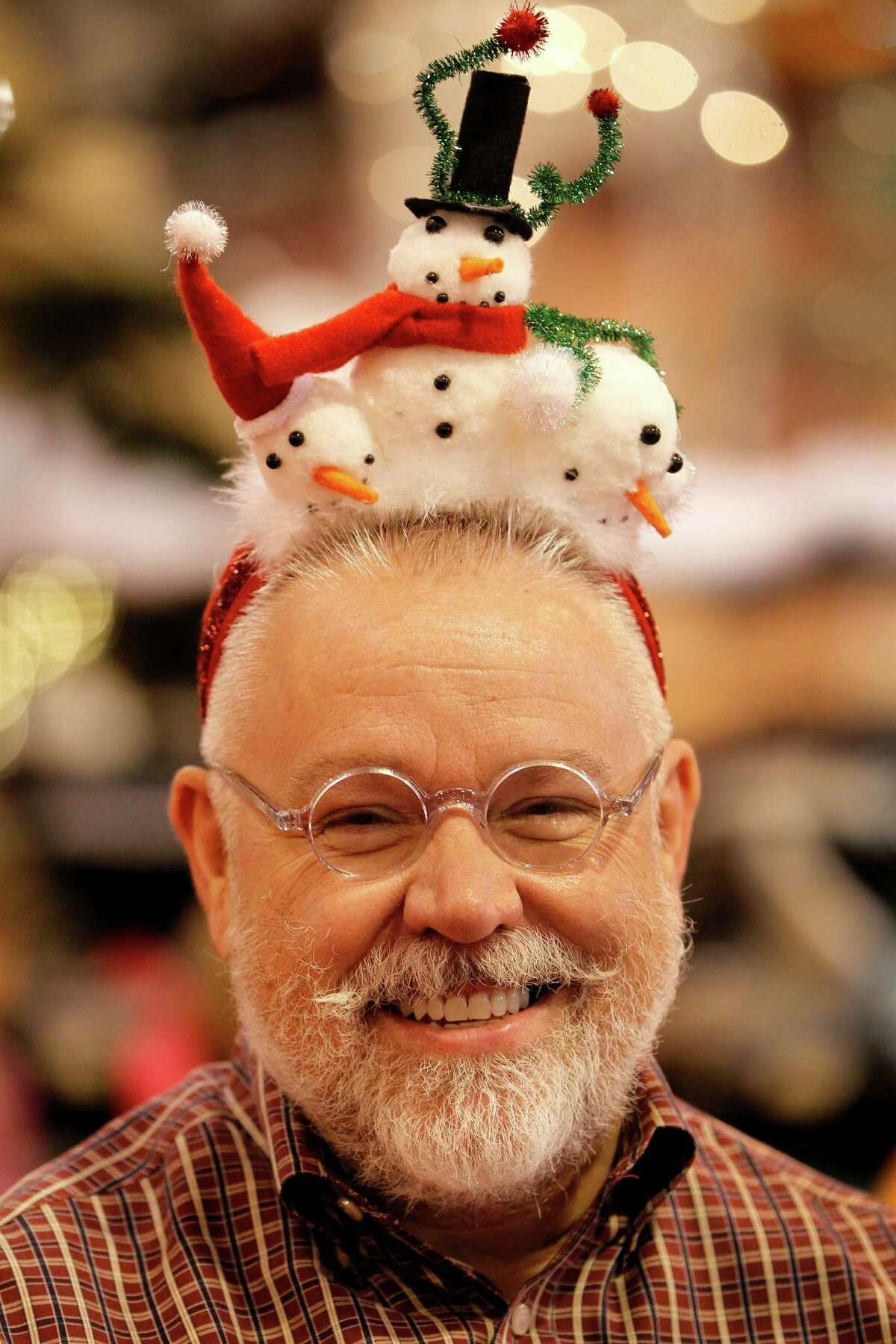 William Houghton wears festive headwear while working in the Campbell Davis Associates booth at the Nutcracker Market on Saturday, Nov. 14, 2015, in Houston.
