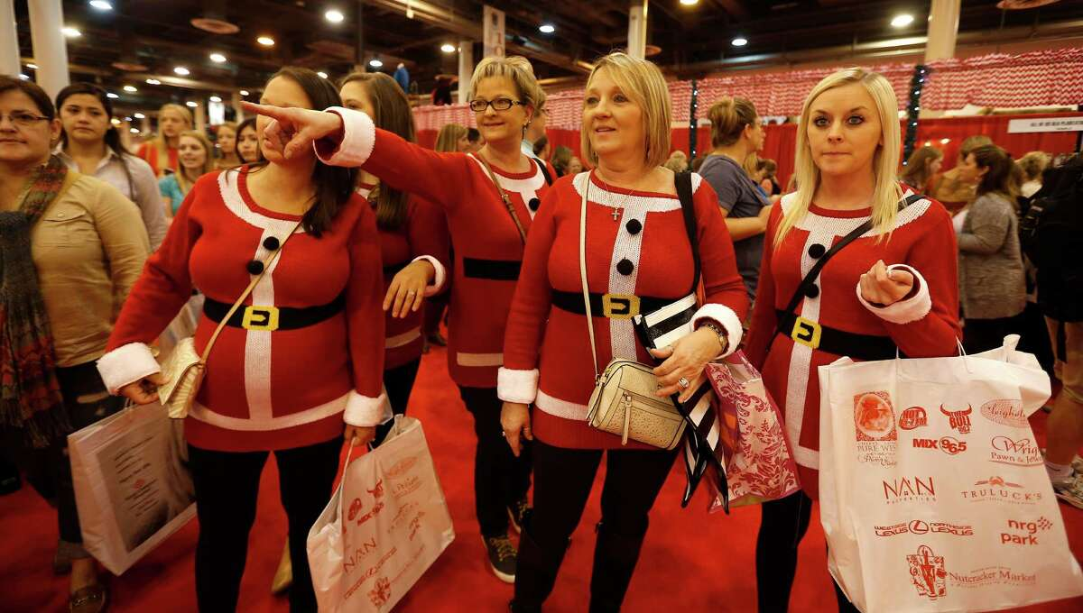Roxana McGee points out an item to her sister, Meloney Bauer Kemper, as they shop with Larissa Eisenmenger, left, and Stephanie Casey, right, who all dressed alike to shop at the Nutcracker Market on Saturday, Nov. 14, 2015, in Houston.