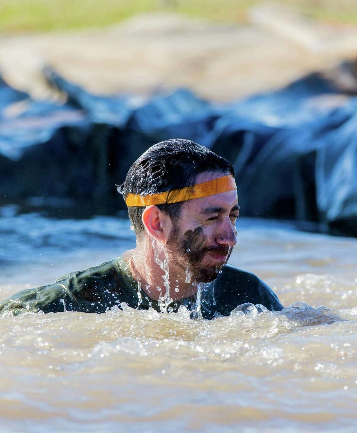 A muckers reacting as he comes up for air in a pool of muddy water during the MuckFest at Royal Purple Raceway, Saturday, Nov. 14, 2015, in Baytown.