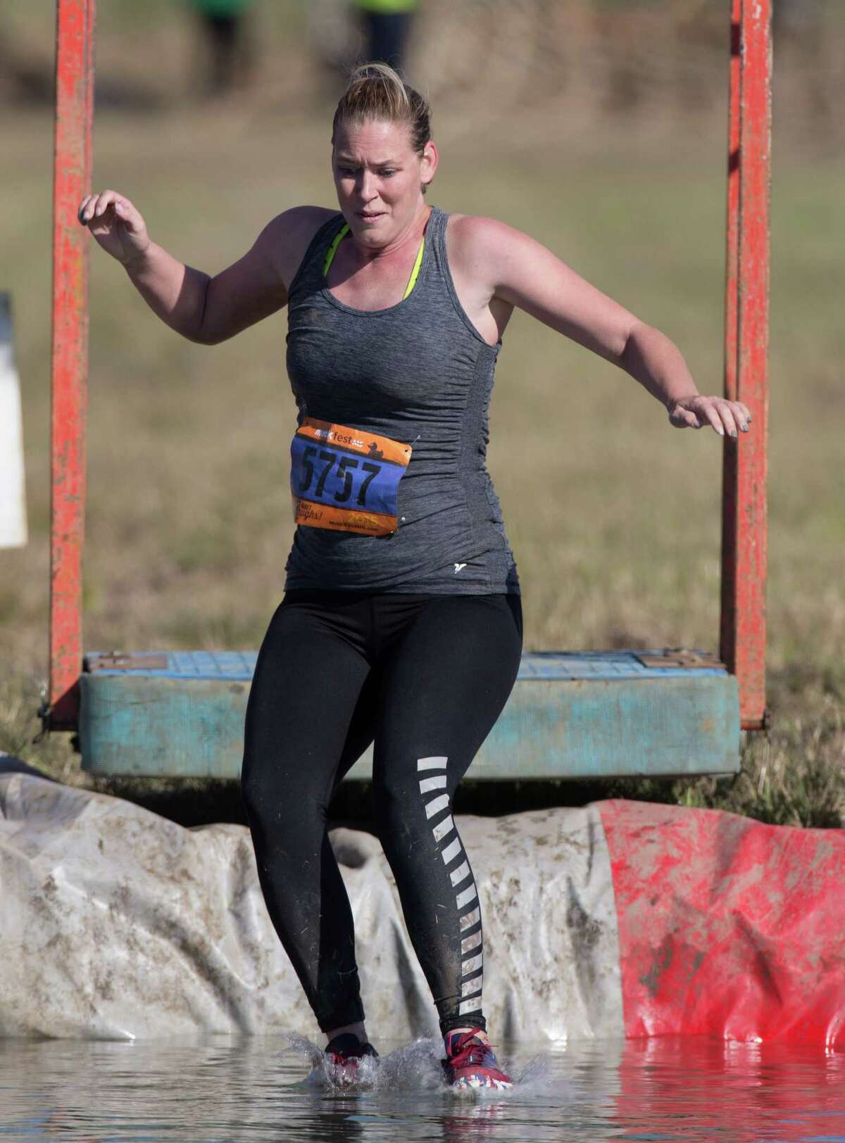 A muckers takes the plunged in a pool of muddy water during the MuckFest at Royal Purple Raceway, Saturday, Nov. 14, 2015, in Baytown.