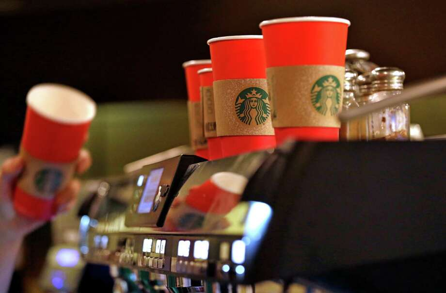 A barista reaches for a red paper cup as more, with cardboard liners already attached, line the top of an espresso machine at a Starbucks coffee shop in the Pike Place Market, Tuesday, Nov. 10, 2015, in Seattle.  Photo: Elaine Thompson, AP / AP
