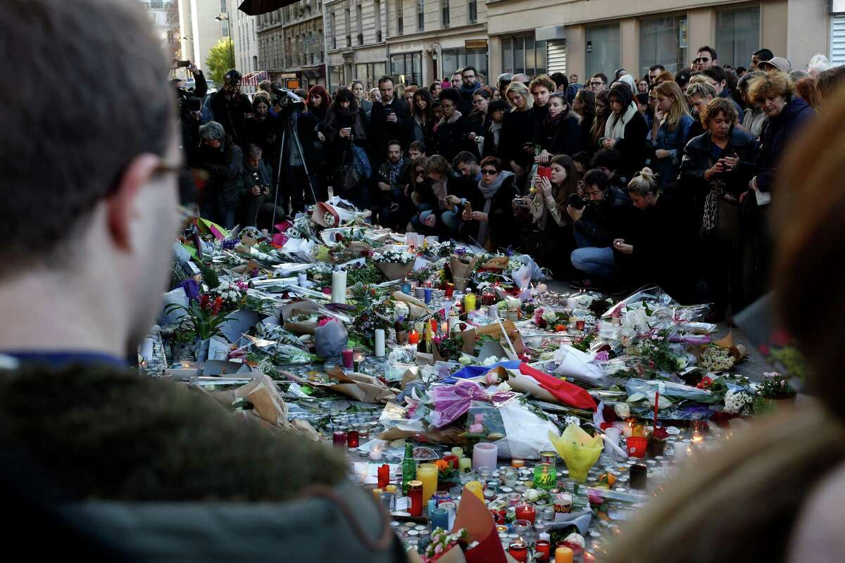 People gather at the Carillon cafe in Paris, France, Sunday Nov. 15, 2015, two days after over 120 people were killed in a series of shooting and explosions. French troops deployed around Paris on Sunday and tourist sites stood shuttered in one of the most visited cities on Earth while investigators questioned the relatives of a suspected suicide bomber involved in the country's deadliest violence since World War II.Latest from AP: Officials: Manhunt for suspected Paris attacker on the run