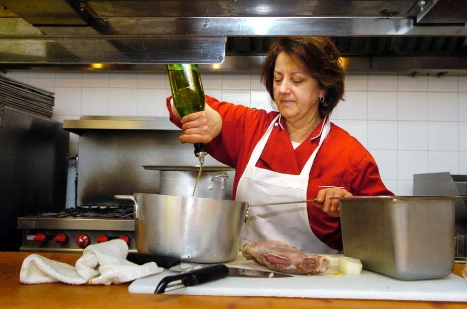 Maria Marchetti cooks Caldariello, a dish of wild greens and lamb, at her restaurant Columbus Park Trattoria in Stamford, Conn. on Thursday March 25, 2010. She pours extra virgin oil into the pan to braise the lamb shank and onions. Photo: Dru Nadler / Stamford Advocate