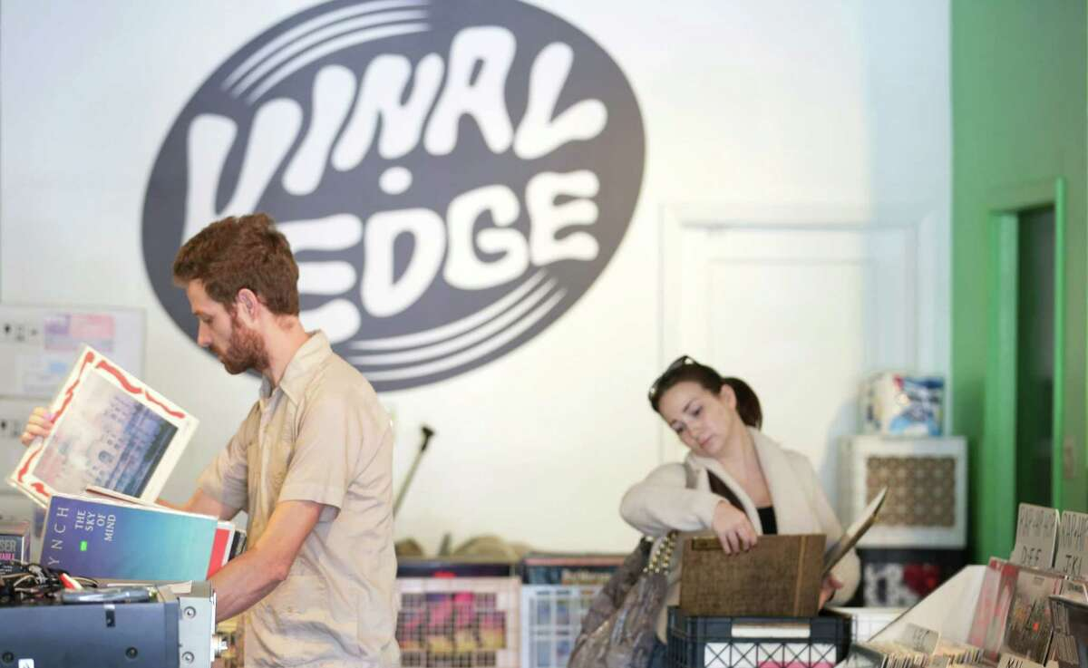 """Richard Johnson, left, and Amber Hyde, right, look through crates of records at Vinal Edge in the Heights, Saturday, Nov. 14, 2015, in Houston. """"[It's] strictly about used records,"""" Johnson said. Hyde had bought a record player that morning and was starting her collection."""