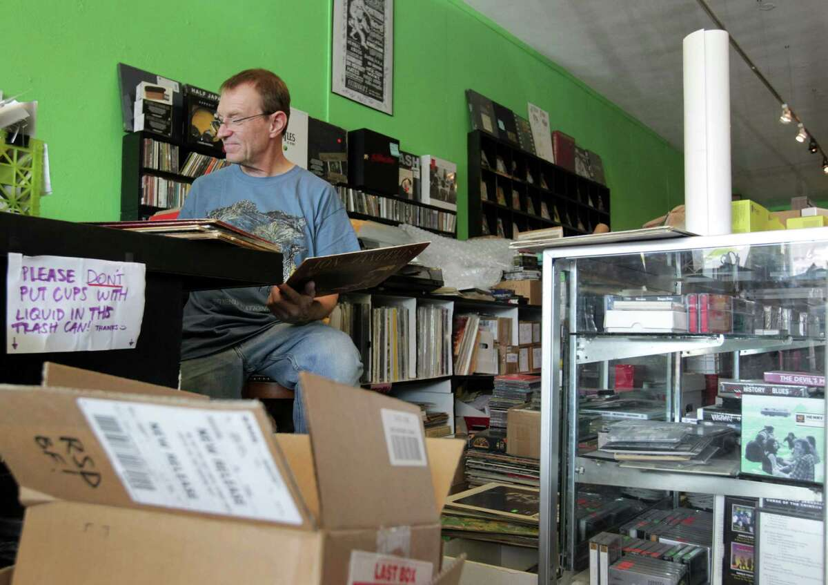 Chuck Roast, owner of Vinal Edge, prices used records at his store in the Heights, Saturday, Nov. 14, 2015, in Houston.