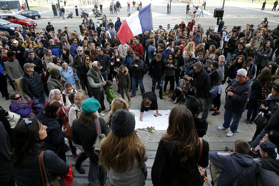 A woman signs a poster as the crowd grows during a memorial for the victims of the terrorist attacks in Paris at City Hall in San Francisco, California, on Sunday, Nov. 15, 2015. Photo: Connor Radnovich, The Chronicle
