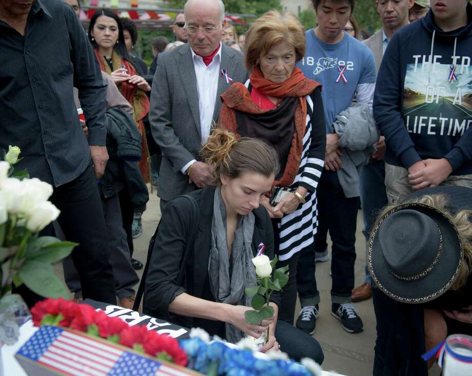 UTSA International student Mathilde Hergott from France places a candle and a flower at a vigil for the victims of shooting and bombing attacks on the people of Paris held in the Main Plaza outside San Fernando Cathedral in San Antonio on Sunday, November 15, 2015. Photo: Matthew Busch / For The San Antonio Express-News / © Matthew Busch