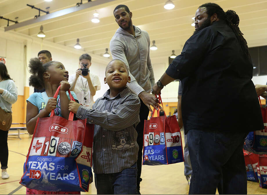 Montrinique Ali, 7, left, and her brother, Dereon Taylor, 6, carry their turkey dinner given to them by San Antonio Spurs forward LaMarcus Aldridge, in back, at the Boys and Girls of San Antonio Eastside Branch, Sunday, Nov. 15, 2015. Aldridge teamed up with H-E-B to give 200 Boys and Girls Club families a Thanksgiving dinner of turkey and trimmings. The families were also treated to Thanksgiving prep party that included arts & crafts and participating in a recipe demonstration. On the right is Kevin Shandy, assistant director of the Eastside branch. Photo: Jerry Lara /San Antonio Express-News / © 2015 San Antonio Express-News