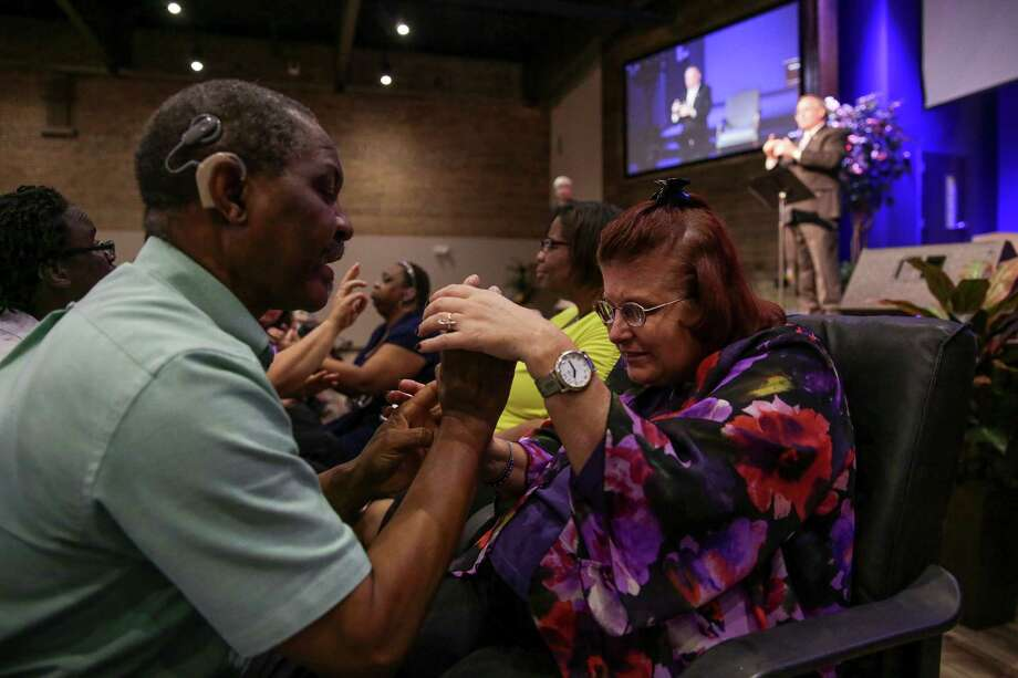LeAnn Cayer holds onto the hands of tactile signer Kunle Adegboye as he translates the sermon to her Sunday at Woodhaven Baptist Deaf Church. Photo: Michael Ciaglo, Staff / © 2015  Houston Chronicle