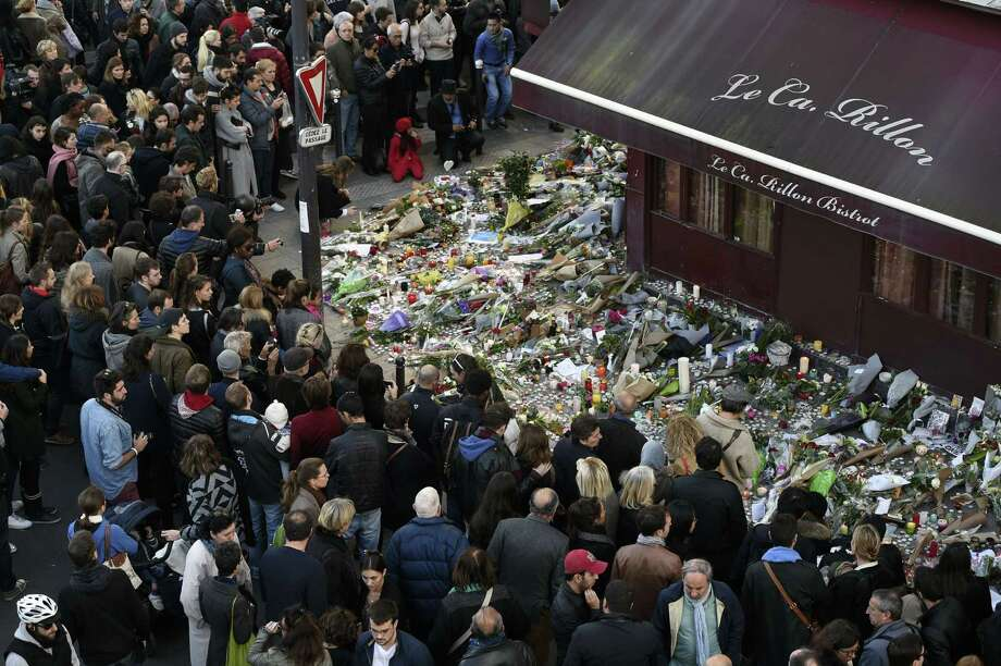 """TOPSHOTS People gather at a makeshift memorial in front of """"Le carillon"""" restaurant on November 16, 2015, in the 10th district of Paris, following a series of coordinated terrorists attacks on November 13. Islamic State jihadists claimed a series of coordinated attacks by gunmen and suicide bombers in Paris that killed at least 128 people in scenes of carnage at a concert hall, restaurants and the national stadium. AFP PHOTO / ALAIN JOCARDALAIN JOCARD/AFP/Getty Images Photo: ALAIN JOCARD, Staff / AFP / Getty Images / AFP"""