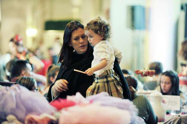 Robin Dalton and her daughter Alice, 2, from Saratoga Springs look over some of the items for sale at the Saratoga Performing Arts Center's Annual Nutcracker Tea on Sunday, Nov. 15, 2015, in Saratoga Springs, N.Y.  Members of the Northeast Ballet Company performed during the event.  The ballet company took part in three performances on Sunday.  The Northeast Ballet Company will perform the full Nutcracker Ballet at Proctors Theater on December 4th, 5th, and 6th.  (Paul Buckowski / Times Union) Photo: PAUL BUCKOWSKI / 00034234A