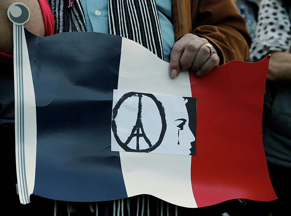 A man holds a sign during Houston Home and Houston-Nice sister city moment of contemplation at Sam Houston Park mourning the the victims of Friday's attacks in Paris Sunday, Nov. 15, 2015, in Houston.