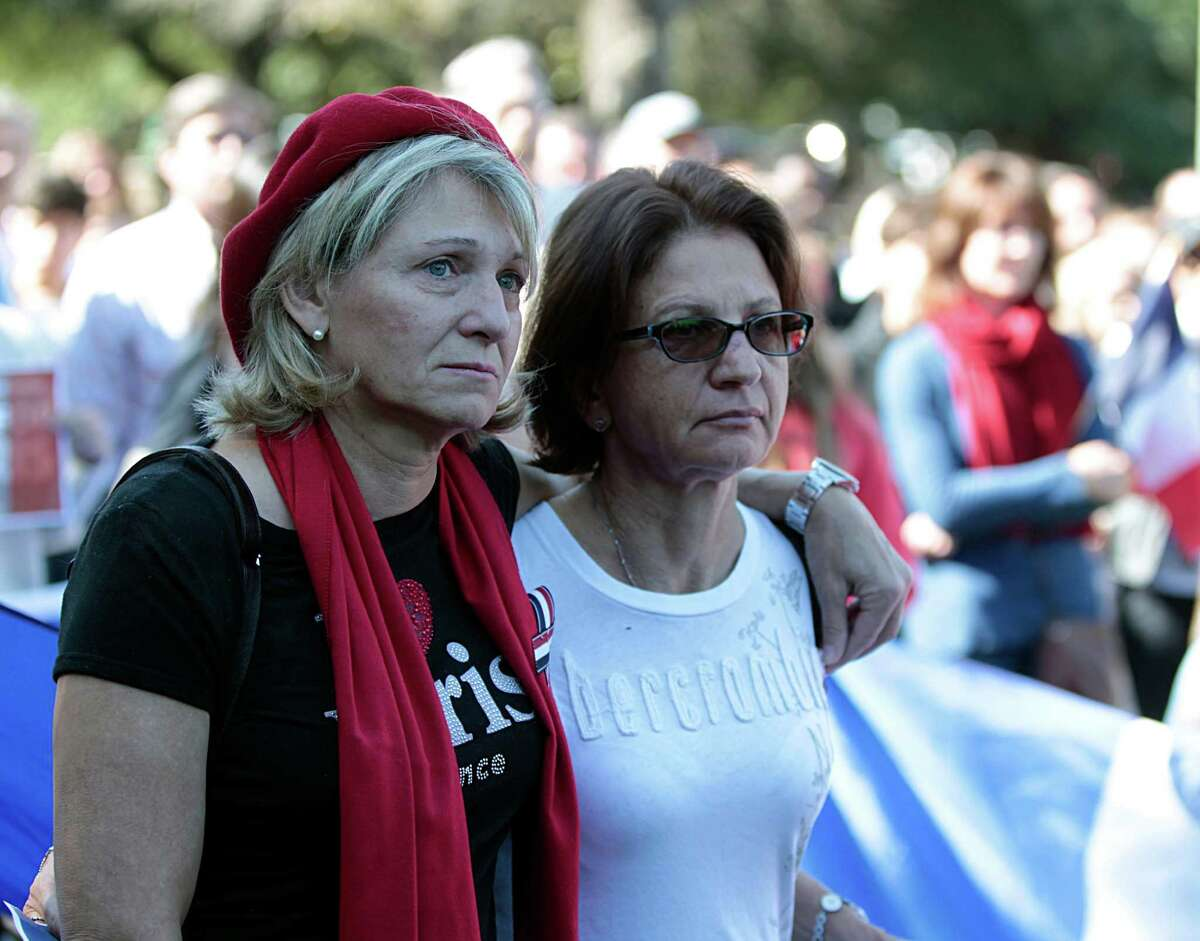 Veronique Moore left, and Francoise Burtz right, during the Houston Home and Houston-Nice sister city moment of contemplation at Sam Houston Park mourning the the victims of Friday's attacks in Paris Sunday, Nov. 15, 2015, in Houston.