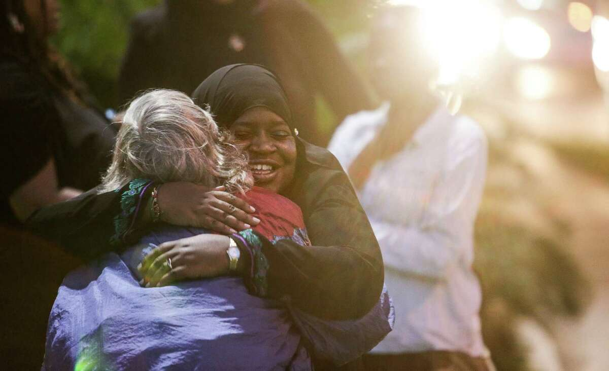 Madinah Al-Beshr, right, gives Judy Emerson a hug after an interfaith prayer for humanity to mourn for the victims of the Paris attacks and condemn the actions of ISIS on the corner of Westheimer Road and Post Oak Boulevard Sunday, Nov. 15, 2015, in Houston. Al-Beshr and Emerson met earlier in the night at the beginning of the vigil held by the Houston branch of the Council on American-Islamic Relations.