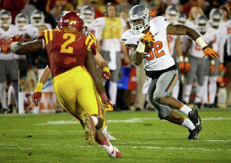 Oklahoma State running back Chris Carson, right, runs the ball during the second half of an NCAA college football game against Iowa State, Saturday, Nov. 14, 2015, in Ames, Iowa. (AP Photo/Justin Hayworth) Photo: Justin Hayworth, FRE / Associated Press / FR170760 AP