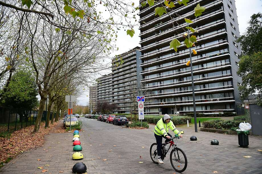A cyclist rides in the area of Brussels' Molenbeek district where police arrested people in connection with the deadly attacks in Paris. Photo: Emmanuel Dunand, AFP / Getty Images