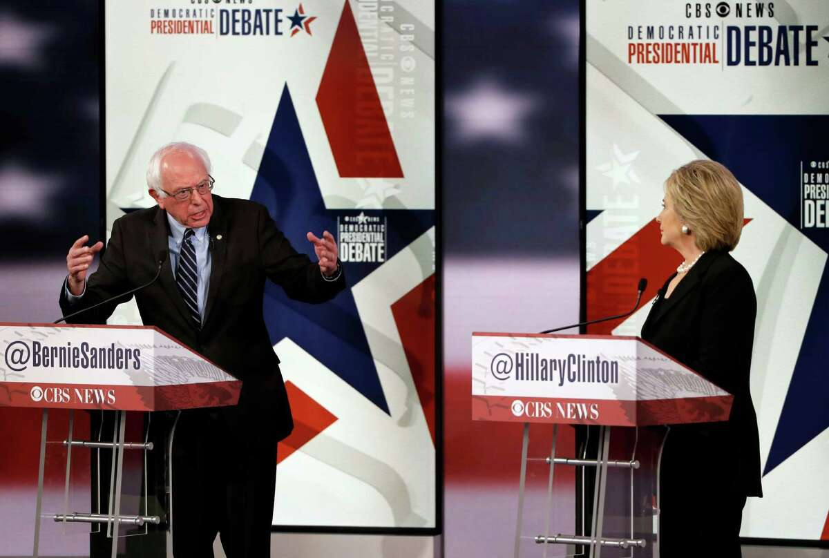Bernie Sanders, left, makes a point as Hillary Rodham Clinton listens during a Democratic presidential primary debate, Saturday, Nov. 14, 2015, in Des Moines, Iowa. (AP Photo/Charlie Neibergall) ORG XMIT: IAKS136