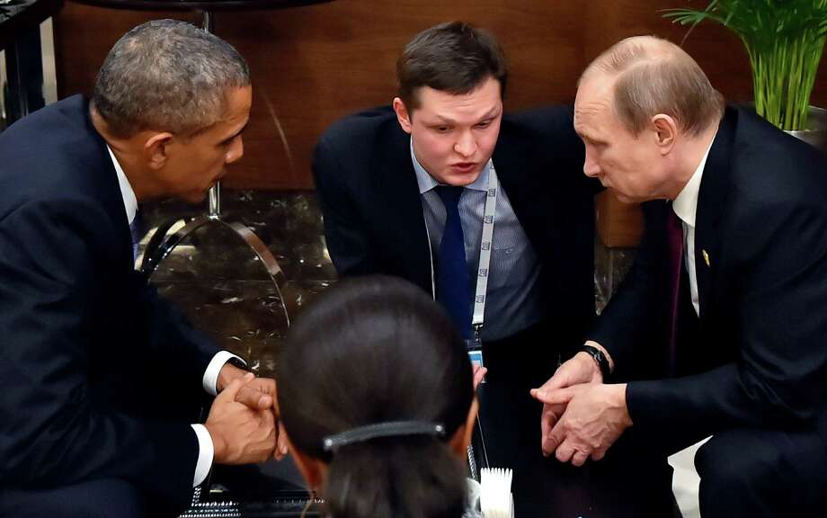 With a translator between them, President Barack Obama speaks with Russian President Vladimir Putin prior to the opening session of the G-20 summit in Antalya, Turkey. Photo: Associated Press / POOL RIA NOVOSTI KREMLIN
