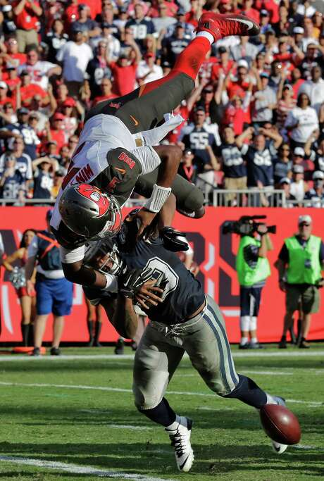 A hit by Cowboys linebacker Anthony Hitchens sends Buccaneers quarterback Jameis Winston and the football flying in different directions. Photo: Chris O'Meara, STF / AP