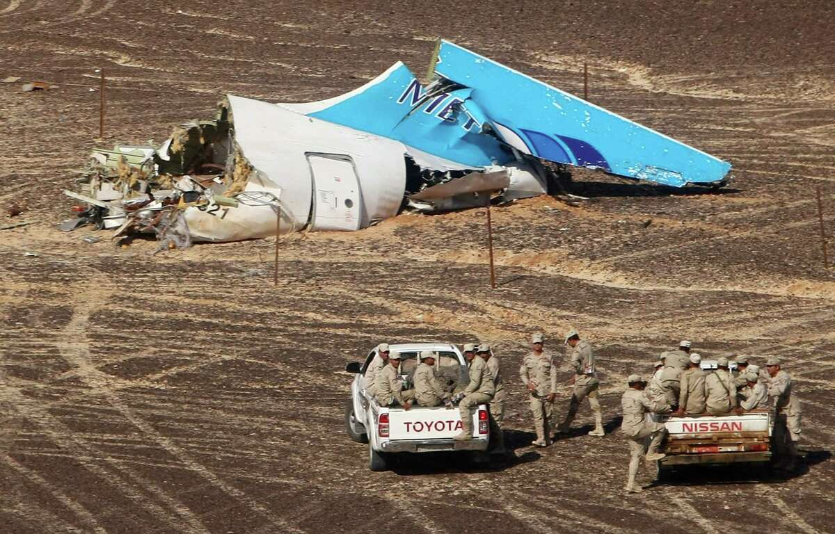 FILE - In this file photo made available Monday, Nov. 2, 2015, and provided by Russian Emergency Situations Ministry, Egyptian Military on cars approach a plane's tail at the wreckage of a passenger jet bound for St. Petersburg in Russia that crashed in Hassana, Egypt, on Sunday, Nov. 1, 2015. After the Islamic State group claimed the downing of the Russian plane in Egypt and deadly suicide bombings in Lebanon and Turkey, the Paris attacks appear to signal a fundamental shift in strategy toward a more global approach that experts suggest is likely to intensify. (Maxim Grigoriev/Russian Ministry for Emergency Situations via AP, FILE) ORG XMIT: CAIBS103