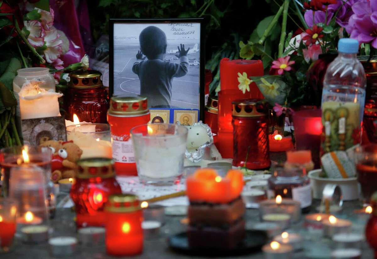 FILE - In this Monday, Nov. 2, 2015, file photo, a portrait of 10 month Darina Gromova, a victim of a plane crash, is surrounded by flowers and candles at an entrance of Pulkovo airport outside St. Petersburg, Russia. Coming soon after the Islamic State group claimed the downing of the Russian plane in Egypt and deadly suicide bombings in Lebanon and Turkey, the Paris attacks appear to signal a fundamental shift in strategy toward a more global approach that experts suggest is likely to intensify. (AP Photo/Dmitry Lovetsky, File) ORG XMIT: CAIBS106