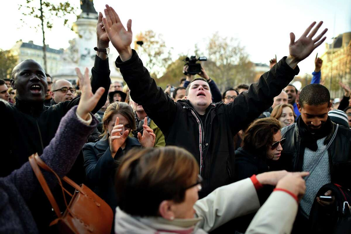 PARIS, FRANCE - NOVEMBER 15: People gather and sing songs at Place de la Republique as France observes three days of national mourning for the victims of the terror attacks on November 15, 2015 in Paris, France. As France observes three days of national mourning members of the public continue to pay tribute to the victims of Friday's deadly attacks. A special service for the families of the victims and survivors is to be held at Paris's Notre Dame Cathedral. (Photo by Jeff J Mitchell/Getty Images) ORG XMIT: 591817963