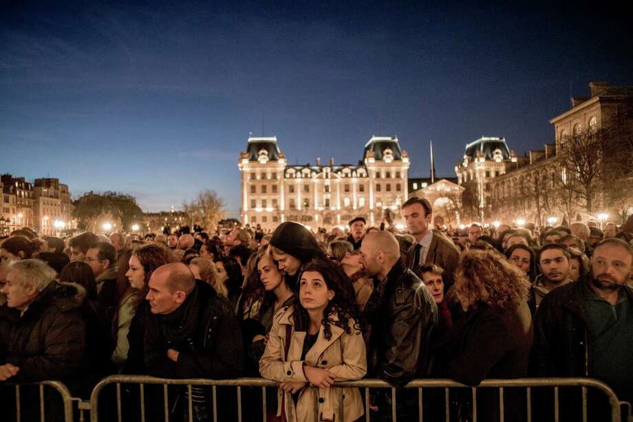 Mourners gather outside a service at Notre Dame Cathedral two days after terror attacks killed at least 129 people in Paris. Photo: TOMAS MUNITA, STR / NYTNS