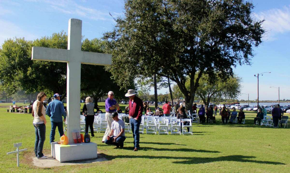 A group gathers around at Port Neches' Riverfront Park before a vigil to honor a cross the Freedom From Religion Foundation is trying to remove.