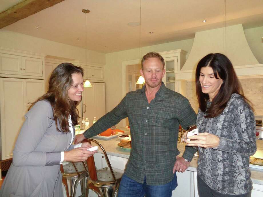 Actor Ian Ziering of television series fame on Beverly Hills, 90210 and movie stardom in the Sharknado series, was in Fairfield Friday promoting an anti-aging skin care and lifestyle line of products at an event hosted by Julie Vanderblue of the Vanderblue Team, an affiliate of Higgins Group Real Estate; here Zierling and Vanderblue (left) learn about one of Nu Skin's products from local independent distributor Laura Kall Felton of Westport Photo: Meg Barone / Meg Barone / Connecticut Post