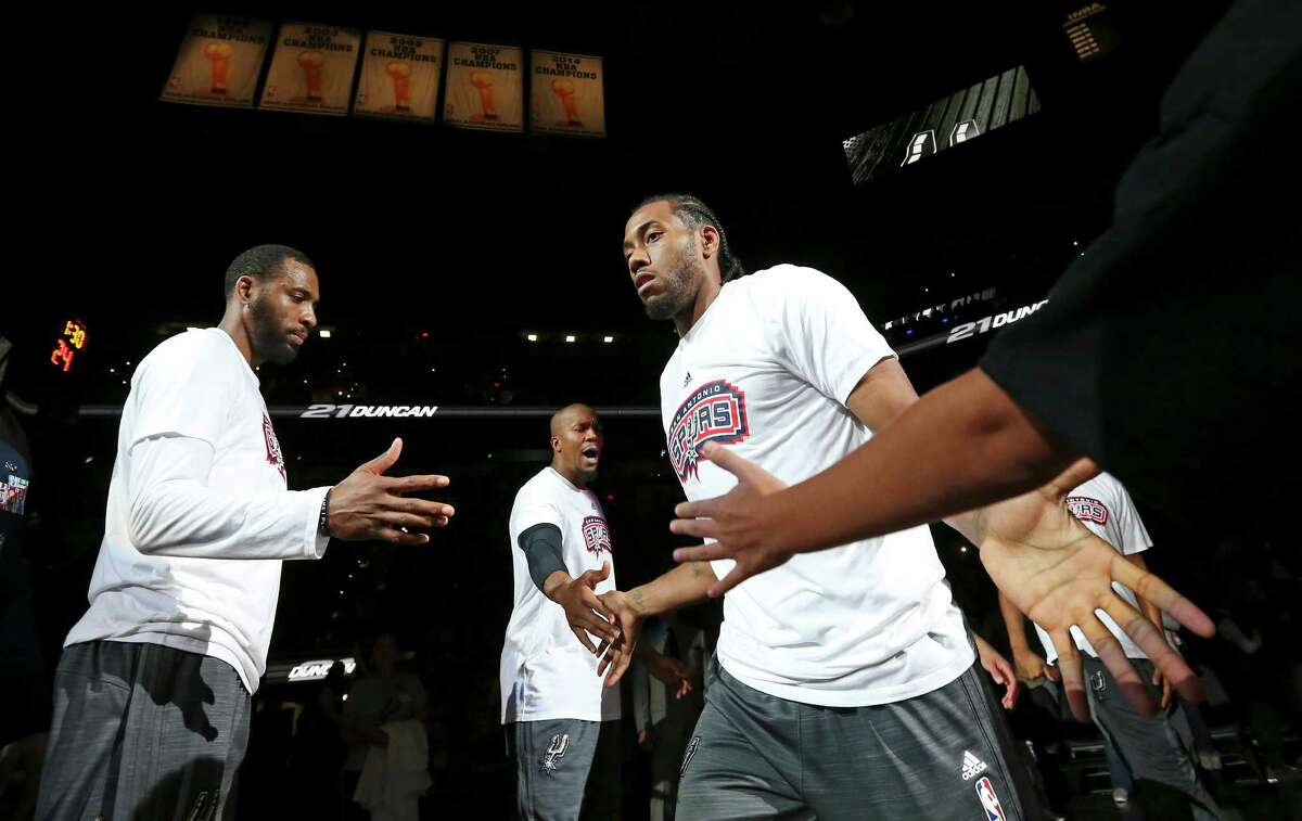 Spurs' Kawhi Leonard (right) is introduced as Rasual Butler (left), and David West look on before the game with the Charlotte Hornets on Nov. 7, 2015 at the AT&T Center.