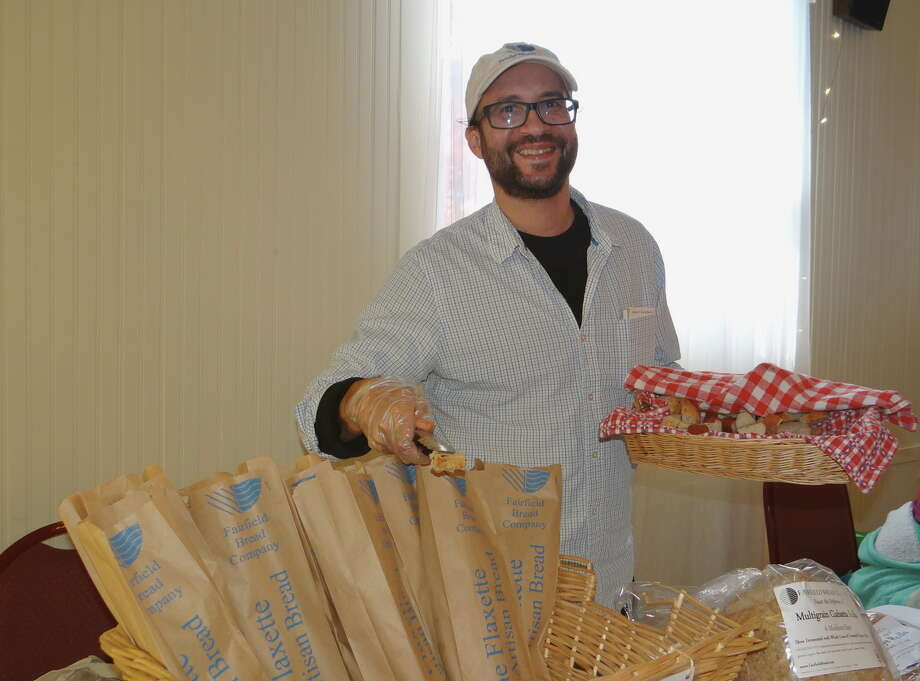 Michael Mordecai of Fairfield Bread Company offers samples of Raisin Rye Rolls at the Winter Farmers Market at the Ukrainian American Club Hall of Southport Saturday. Photo: Mike Lauterborn / Mike Lauterborn / Connecticut Post