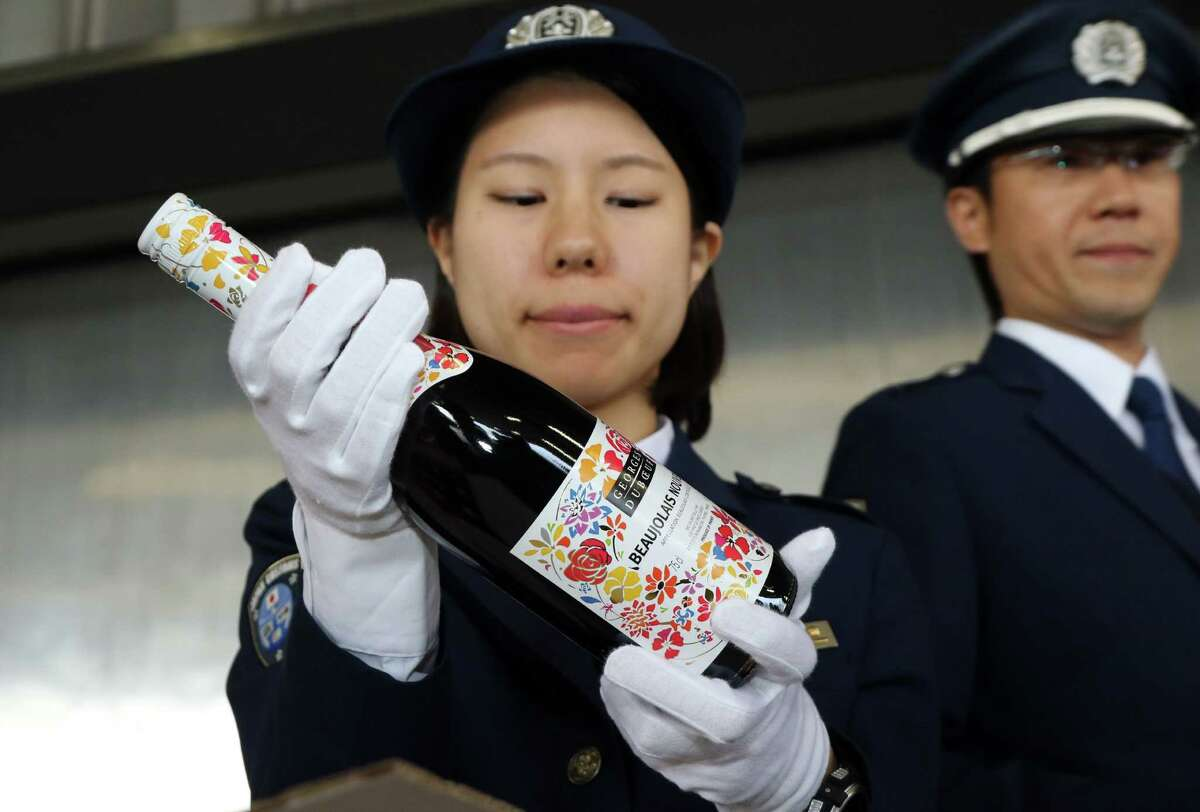 Japanese customs officers check a bottle of 2015 Beaujolais Nouveau wine shortly after its arrival at Tokyo's Haneda Airport on October 31, 2015. The first cargo of 3,200 bottles arrived from Paris for November 19 when the embargo on the wine will be removed.