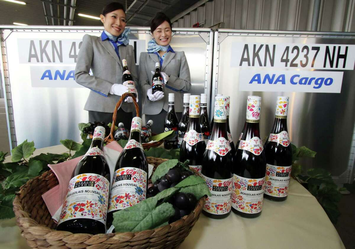 All Nippon Airways (ANA) employees display bottles of 2015 Beaujolais Nouveau wine shortly after the arrival of the bottles at Tokyo's Haneda Airport on October 31, 2015. The first cargo of 3,200 bottles arrived from Paris for November 19 when the embargo on the wine will be removed.