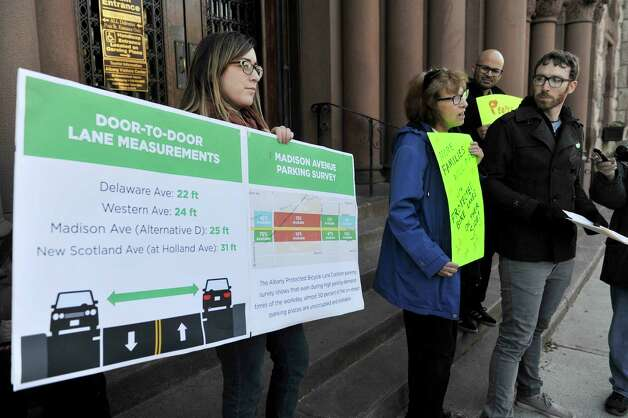 Albany Protected Bicycle Lane Coalition members, Erin Reale, left, of Albany, Virginia Hammer, second from left, of Albany, Jason D'Cruz, third from left, from Albany, and Jim Maximowicz, also from Albany, take part in a protest outside city hall on Monday, Nov. 16, 2015, in Albany, N.Y.  The organizers of the event were calling for protected bicycle lanes on Madison Ave.  (Paul Buckowski / Times Union) Photo: PAUL BUCKOWSKI / 00034249A