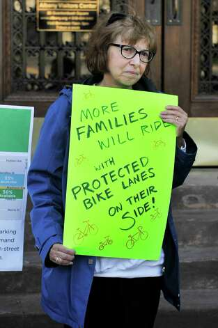 Albany Protected Bicycle Lane Coalition member, Virginia Hammer, holds a sign as she takes part in a protest outside city hall on Monday, Nov. 16, 2015, in Albany, N.Y.  The organizers of the event were calling for protected bicycle lanes on Madison Ave.  (Paul Buckowski / Times Union) Photo: PAUL BUCKOWSKI / 00034249A
