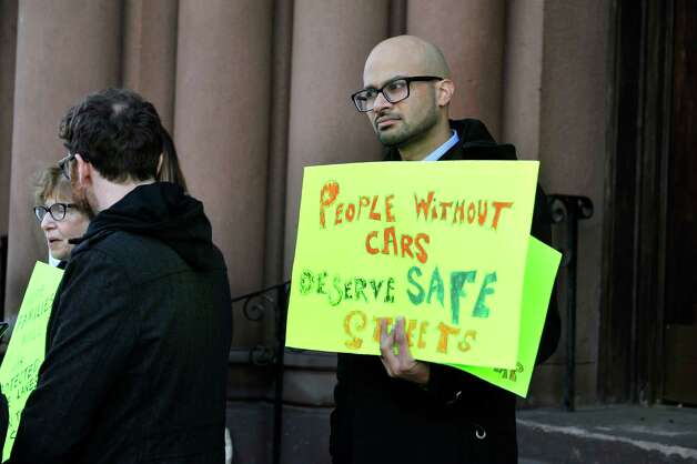 Albany Protected Bicycle Lane Coalition member, Jason D'Cruz, holds a sign as he takes part in a protest outside city hall on Monday, Nov. 16, 2015, in Albany, N.Y.  The organizers of the event were calling for protected bicycle lanes on Madison Ave.  (Paul Buckowski / Times Union) Photo: PAUL BUCKOWSKI / 00034249A
