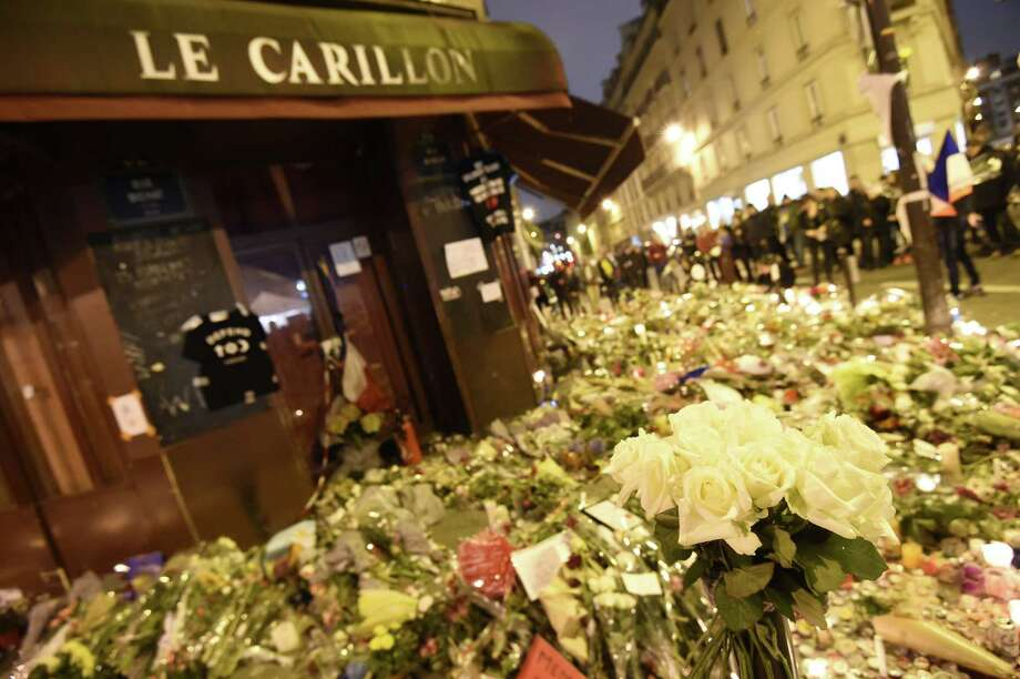 People walk past flowers and candles placed outside Le Carillon cafe on Monday in tribute to the victims of the Paris attacks — claimed by the Islamic State. The attacks killed at least 129 people and left more than 350 injured. Photo: MIGUEL MEDINA /AFP / Getty Images / MIGUEL MEDINA