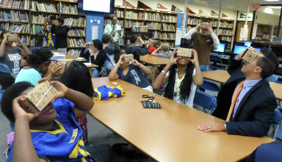 Eighth-graders at Cloonan Middle School took a virtual tour around the world using the latest technology from Google — a cardboard box with 3-D glasses that provides virtual reality when used with a smart phone. Photo: Stamford Public Schools / Contributed Photo