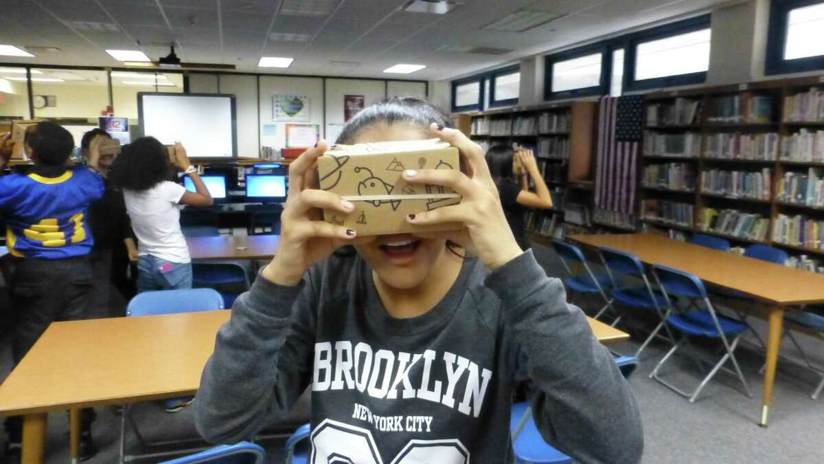 A Cloonan Middle School eighth grader enjoys her Google Cardboard, which provided a virtual your around the world, and the moon.