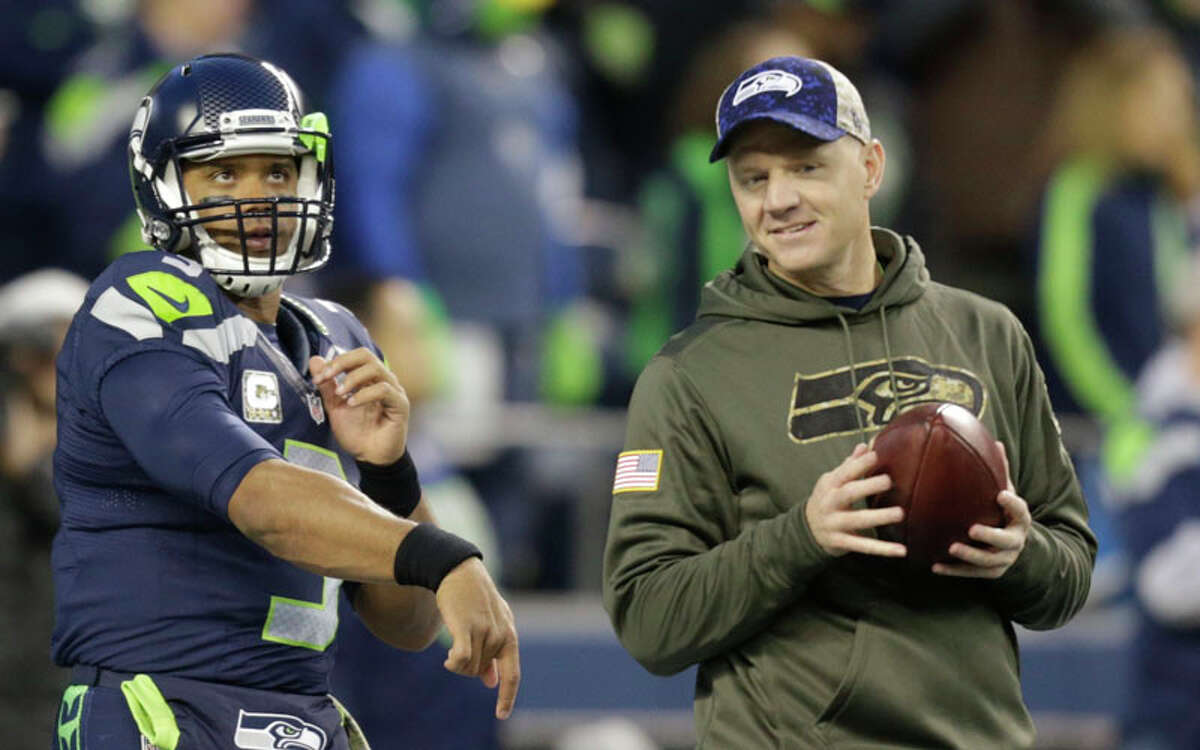 Seattle Seahawks quarterback Russell Wilson, left, passes as Seahawks offensive coordinator Darrell Bevell, right, looks on before an NFL football game against the Arizona Cardinals, Sunday, Nov. 15, 2015, in Seattle. Bevell is wearing a military green sweatshirt as part of the NFL's
