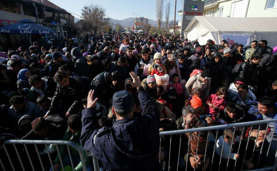 Serbian police officer attempt to organise migrants queuing to get registered at a refugee center in the southern Serbian town of Presevo, Monday, Nov. 16, 2015. Refugees fleeing war by the tens of thousands fear the Paris attacks could prompt Europe to close its doors, especially after police said a Syrian passport found next to one attacker's body suggested its owner passed through Greece into the European Union and on through Macedonia and Serbia last month. (AP Photo/Darko Vojinovic) Photo: Darko Vojinovic / Associated Press / AP